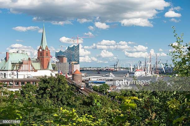 Germany, Hamburg, View of Subway train, Church, Elbphilharmonie and harbour with ship in background