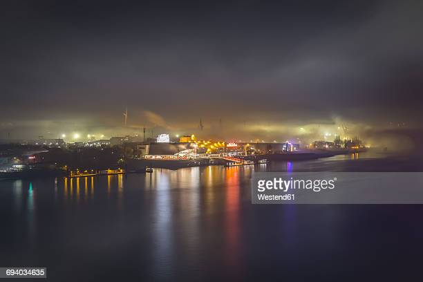 Germany, Hamburg, view to the harbor with lighted musical theater in the fog at night