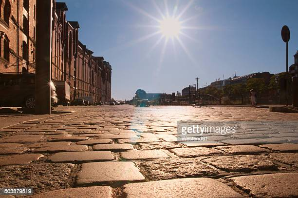 Germany, Hamburg, Warehouse district, Cobblestone pavement in sunlight at Brook 3