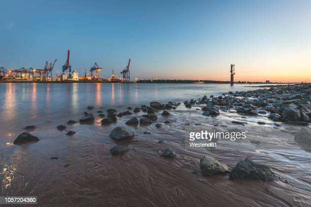 germany, hamburg, wittenbergen, elbe beach in the evening, container harbour in the background - エルベ川 ストックフォトと画像