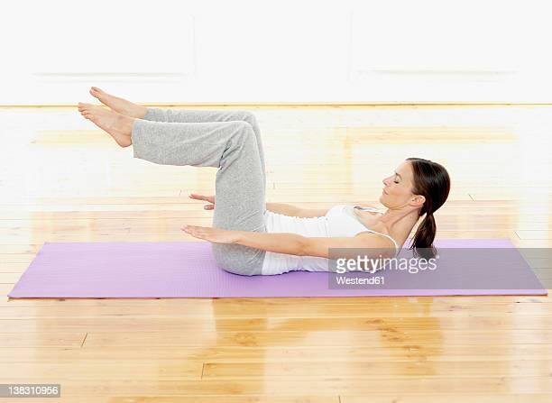 Germany, Hamburg, Woman doing yoga exercise in gym room