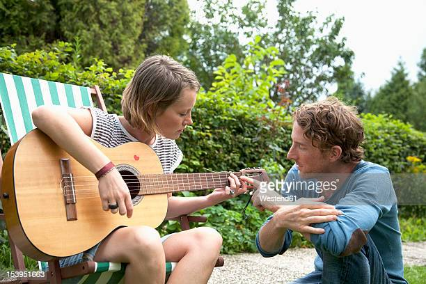 Germany, Hamburg, Woman plucking guitar, man sitting beside in allotment garden