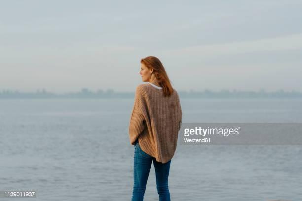 germany, hamburg, woman standing at the elbe shore - wegsehen stock-fotos und bilder