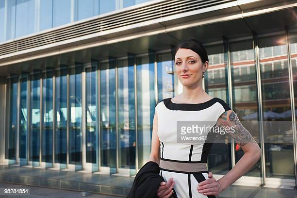 Germany, Hamburg, Woman standing in front of office building, smiling, portrait
