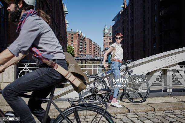 germany, hamburg, woman with electric bicycle watching man passing by on bicycle - moving past stock photos and pictures