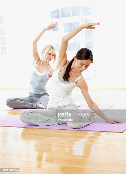 Germany, Hamburg, Yoga instructor and woman doing yoga exercise in gym room