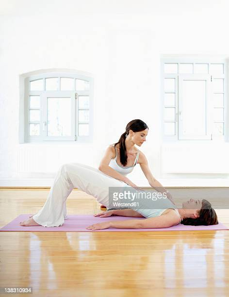 Germany, Hamburg, Yoga instructor helping woman doing yoga exercise in gym room