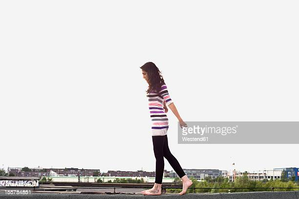 Germany, Hamburg, Young woman balancing on edge of roof