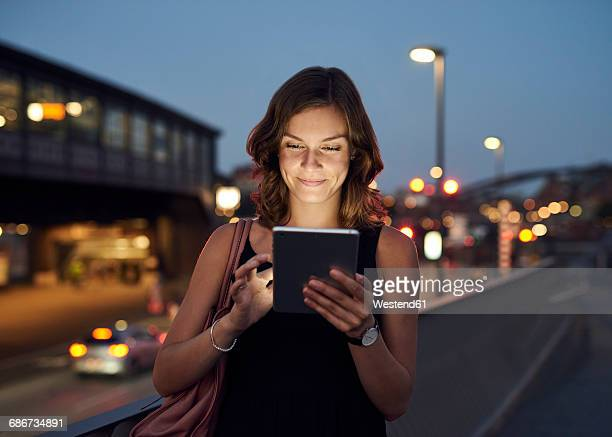 germany, hamburg, young woman in the street using digital tablet - mobilität stock-fotos und bilder