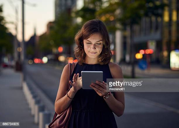 germany, hamburg, young woman in the street using digital tablet - portable information device stock-fotos und bilder