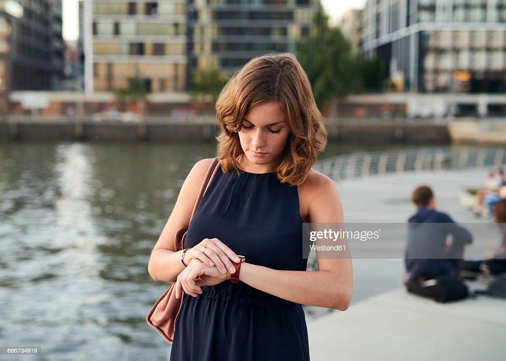 Germany, Hamburg, Young woman looking at watch : Foto de stock
