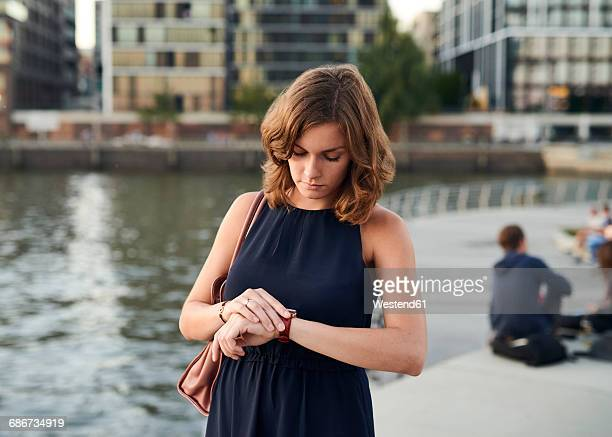 germany, hamburg, young woman looking at watch - ver a hora - fotografias e filmes do acervo