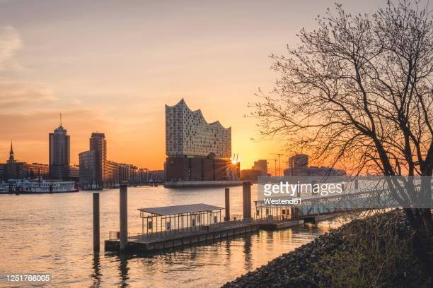 germany, hamburg,empty harbor on bank of elbe river at sunrise withelbphilharmonie in background - amburgo foto e immagini stock