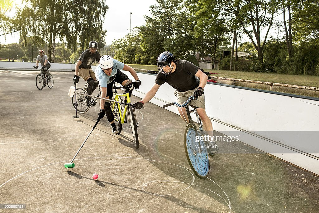 Germany, Hannover, Group of men playing bike polo : Stock Photo