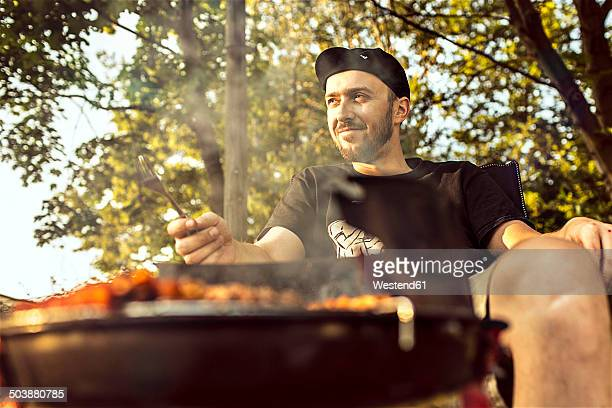Germany, Hannover, Man having a barbecue