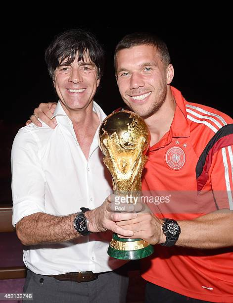 Germany head coach Joachim Loew and Lukas Podolski pose with the World Cup trophy as they celebrate with teammates at a party after winning the 2014...