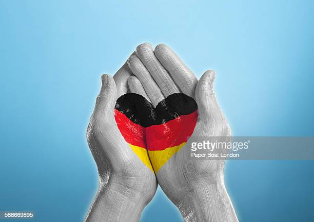 germany heart shaped flag painted on a hand - german flag stock pictures, royalty-free photos & images