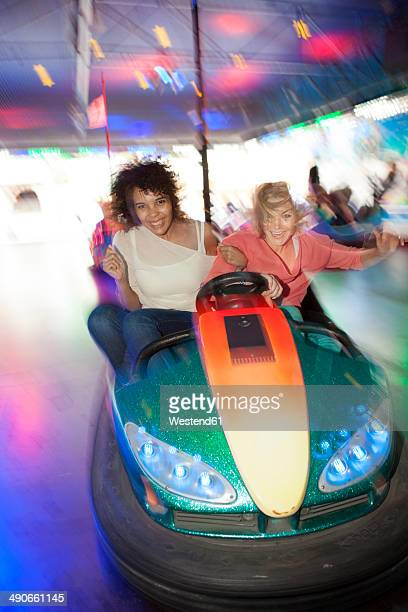Germany, Herne, Two young women riding bumper cars at the fairground