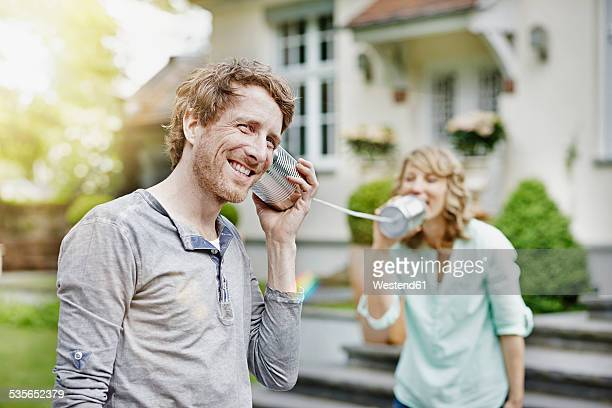Germany, Hesse, Frankfurt, Couple in garden playing with tin can phone