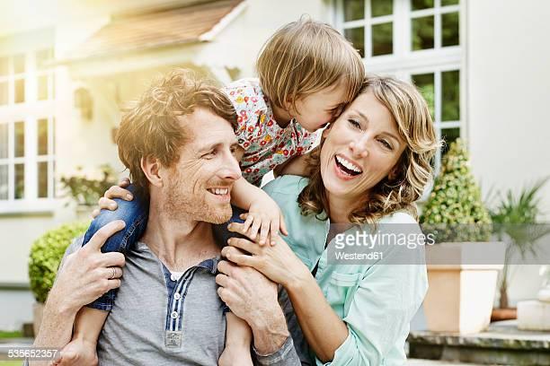 germany, hesse, frankfurt, happy couple with daughter in front of villa - familie mit einem kind stock-fotos und bilder