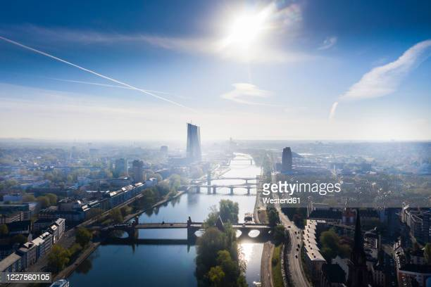 germany, hesse, frankfurt, helicopter view of sun shining over river main and surrounding city buildings - frankfurt am main stock-fotos und bilder