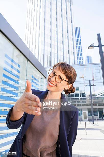 Germany, Hesse, Frankfurt, portrait of greeting businesswoman standing in front of office buildings
