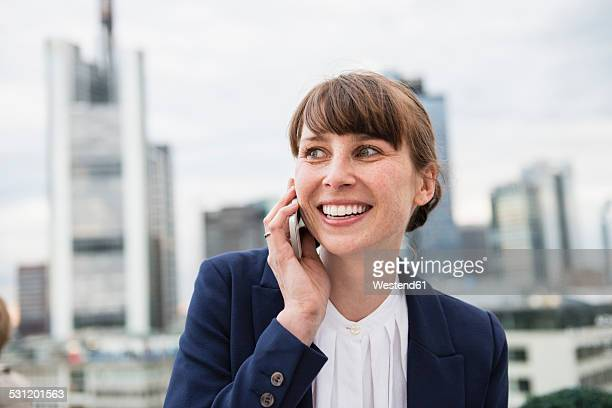 Germany, Hesse, Frankfurt, portrait of smiling businesswoman telephoning in front of skyline