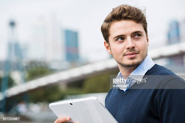 Germany, Hesse, Frankfurt, portrait of smiling young man with digital tablet
