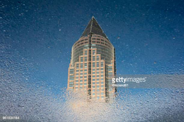 Germany, Hesse, Frankfurt, Trade Fair Tower, mirrored in puddle