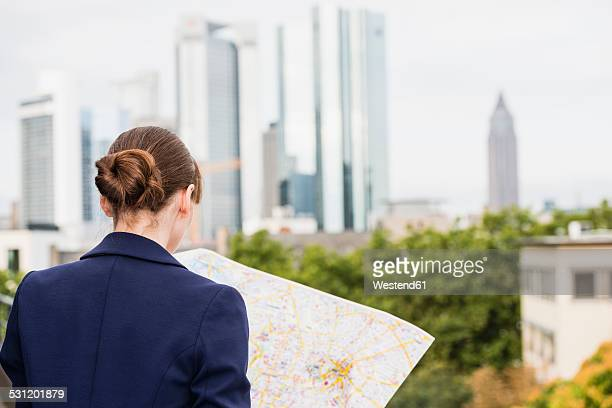 Germany, Hesse, Frankfurt, woman looking at city map, back view