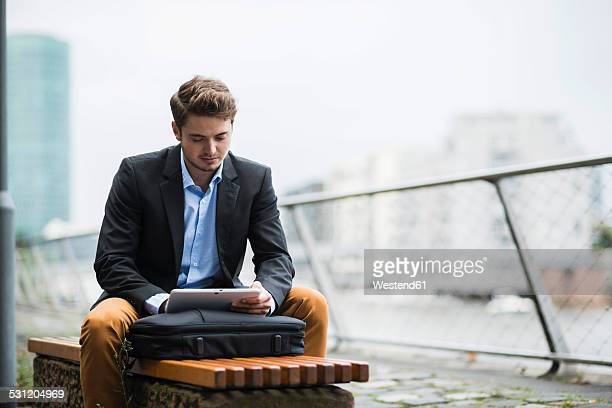 Germany, Hesse, Frankfurt, young man sitting on a bench using his digital tablet