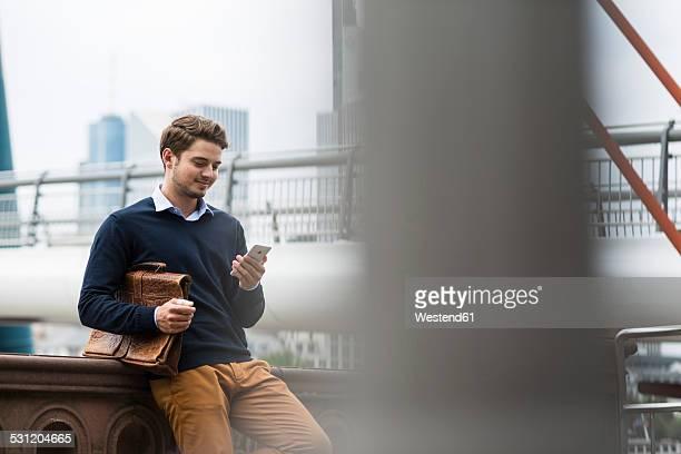 Germany, Hesse, Frankfurt, young man standing on a bridge using smartphone