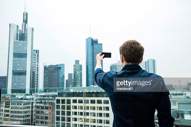 Germany, Hesse, Frankfurt, young man taking a picture of the skyline with his smartphone