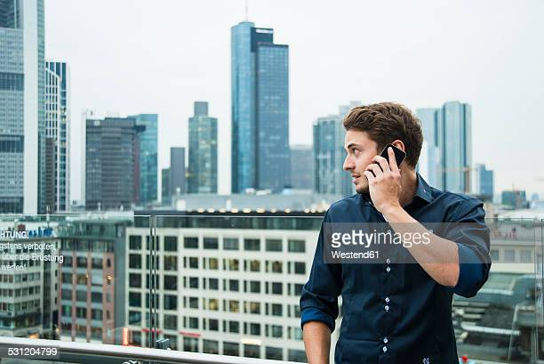 Germany, Hesse, Frankfurt, young man telephoning with his smartphone in front of the skyline