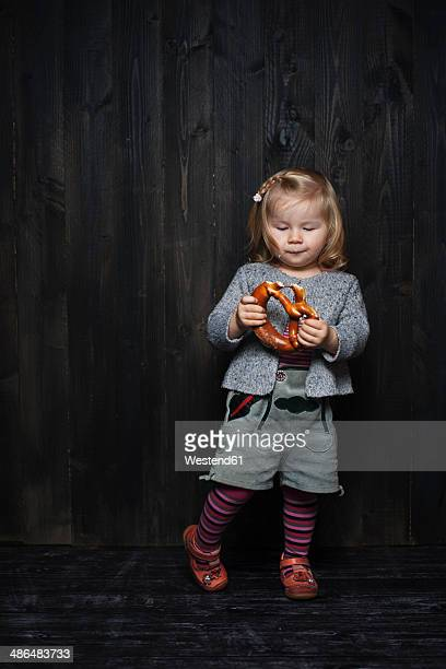 Germany, Hesse, Hofheim, Toddler with Bavarian Leather Shorts and Pretzel