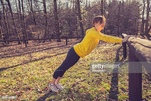 Germany, Hesse, Lampertheim, Woman doing sports in forest, Pushup on a wooden railing