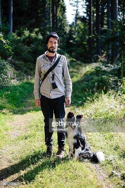 Germany, Hesse, Man with Border Collie on forest path