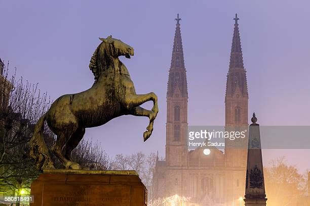 Germany, Hesse, Wiesbaden, Luisenplatz, Horse sculpture of Waterloo Memorial and St. Boniface Church in mist