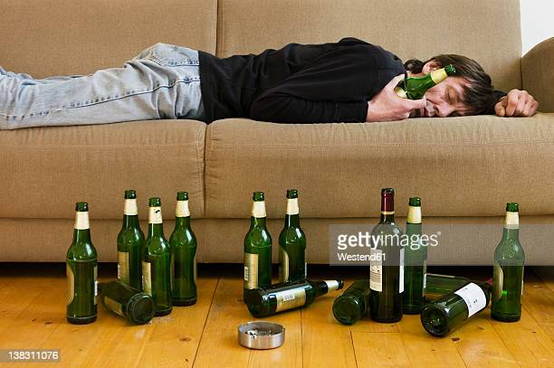 germany, hessen, frankfurt, drunk man lying on sofa with empty beer bottles - binge drinking stock photos and pictures