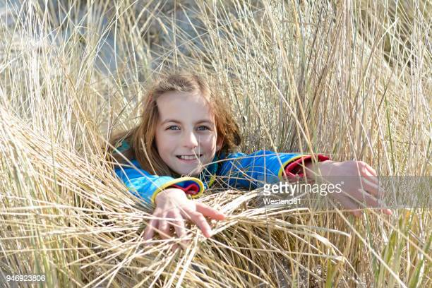 Germany, Hiddensee, portrait of smiling girl lying in grass of dunes