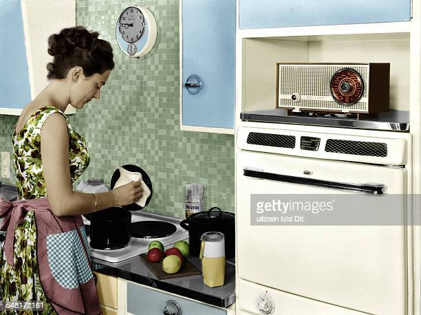 Germany Houswife working in her kitchen right handed a radio by Philips Digitally colorized Original image no 00046059 1959