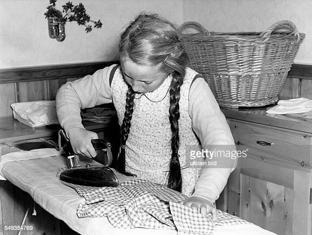 Germany houswork young girl ironing in the fifties