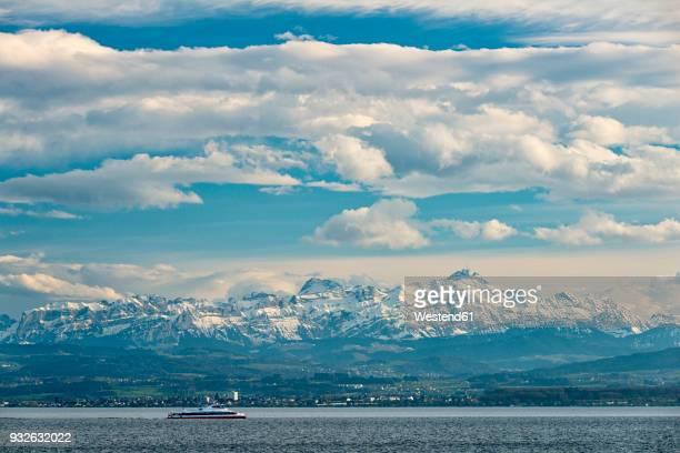 germany, immenstaad, lake constance, catamaran in front of mountainscape - bodenmeer stockfoto's en -beelden