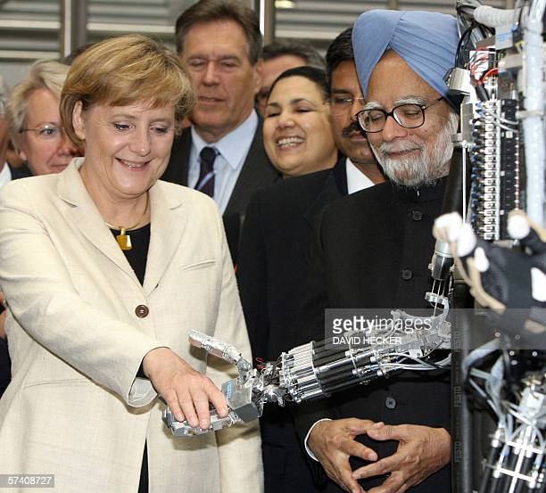 Indian Prime Minister Manmohan Singh looks on as German Chancellor Angela Merkel shakes hands with a robot during a tour of the Hanover Technology...