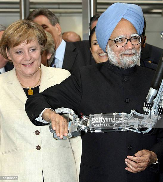 Indian Prime Minister Manmohan Singh shakes hands with a robot as German Chancellor Angela Merkel looks on during a tour of the Hanover Technology...