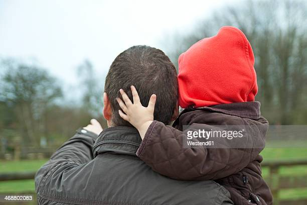 Germany, Kiel, father carries his child in arms