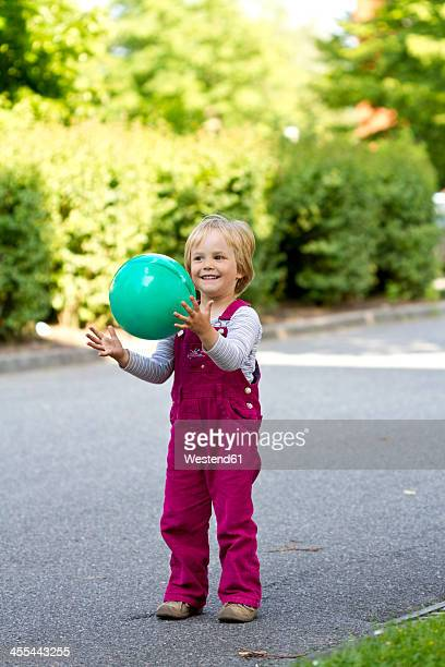 Germany, Kiel, Girl catching green ball, smiling