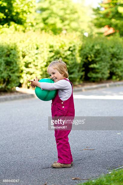Germany, Kiel, Girl holding green ball in her arms, smiling