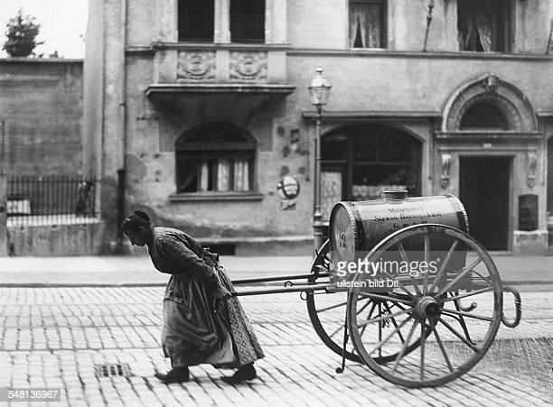 Germany Kingdom Bavaria Munich Woman pulling a cart with a water container to sprinkle the streets around 1900 Photographer Philipp Kester Vintage...