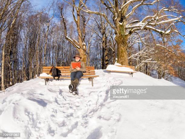 germany, kochel am see, senior man sitting on bench reading e-book in winter - oberbayern stock-fotos und bilder